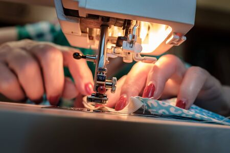 Female hands sew a protective mask using a modern electric sewing machine. Concept of safety during a viral epidemic. Standard-Bild