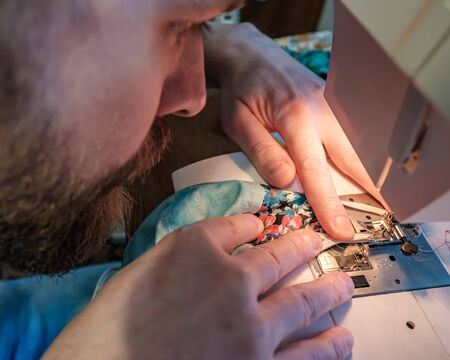 Hands of a concentrated man sew a protective mask using a modern electric sewing machine. Concept of safety during a epidemic.