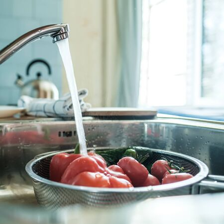 Fresh vegetables under a stream of water in a colander in the sink, in the kitchen, against the background of a towel and a kettle.