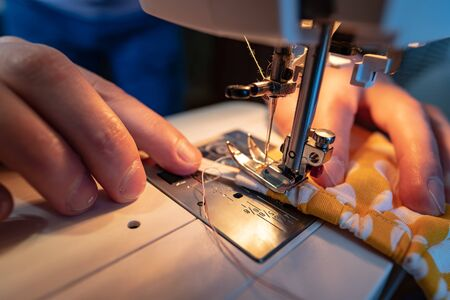 Male hands sew a protective mask using a modern electric sewing machine. Concept of safety during a viral epidemic.