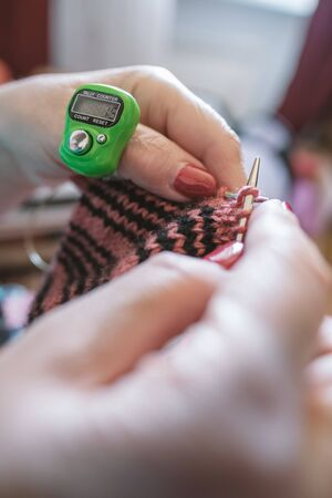 Modern, electronic device for counting loops for hand knitting on knitting needles is worn on the thumb.