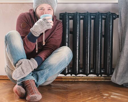 Frozen man in a hat and gloves sits next to a warm radiator and drinks a hot drink, on the floor of the house.
