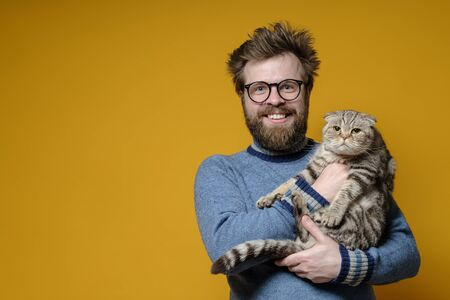 Funny smiling shaggy man hugs his adorable cat, who is not happy that the owner is holding it in hands. Copy space. Standard-Bild