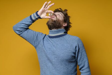 Shaggy, bearded man in a sweater drinks strong alcohol from a wineglass, on a yellow background. Alcoholism concept.