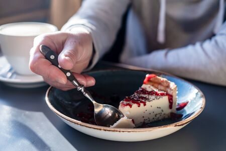Delicious cheesecake breaks off with a spoon from a large piece on a beautiful plate, on a blurred background a cup of cappuccino. Standard-Bild