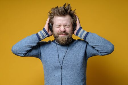 Man in headphones listens to the track and closes eyes in enjoy. Funny hipster music lover in an old sweater. Yellow background.