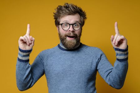 Great idea. Shaggy, bearded man with glasses and a blue sweater raises index fingers up and looks joyfully with mouth open.