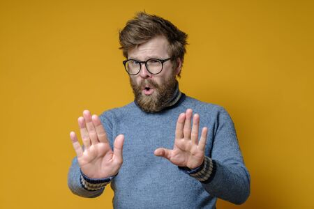 Calm, confident man makes a stop gesture with hands. Shaggy hipster in an old sweater makes a calming signal with palms.