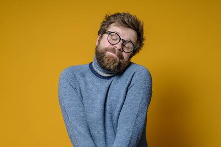 Shy Caucasian man with a shaggy hairstyle and beard modestly folded hands and closed eyes, with a cute expression on face.