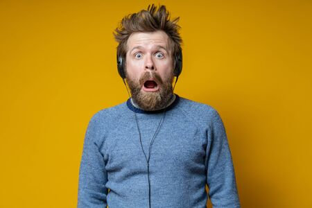 Man in the headphones is shocked. Shaggy music lover in an old sweater fearfully looks with his mouth open. Yellow background.
