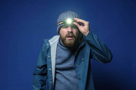 Bearded man with a headlamp in a knitted hat and a waterproof jacket is trying to see something in the light of a flashlight.