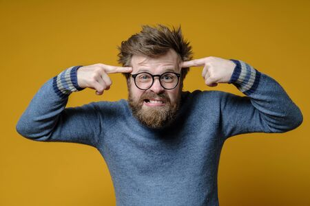 Angry shaggy man with glasses and an old sweater holds index fingers on his temples, proving to interlocutor that he is an idiot.
