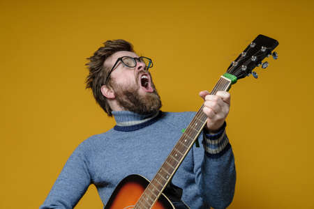 Hipster in an old sweater plays an acoustic guitar and sings loudly, on a yellow background. Hobbies, lifestyle. 免版税图像