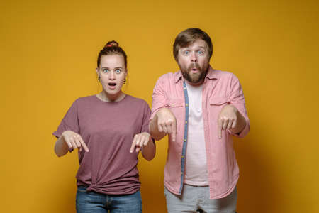 Surprised woman and man point down with their index fingers and stare wide-eyed at the camera, on a yellow background.