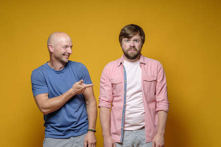 Bald man taunts his upset, unhappy friend and mockingly points finger at him. Bad joke. Archivio Fotografico