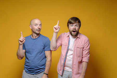 Great idea. Two funny men raise their index fingers up and look at the camera with joy, intrigue.