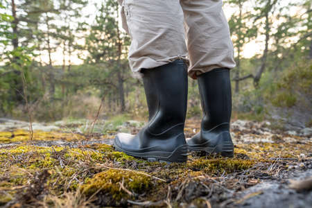Male feet in rubber, waterproof boots, stand in the forest on a summer day. Active lifestyle.