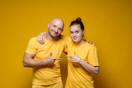 Smiling man and woman in plain, bright clothes hug and point index finger at each other, on a yellow background.