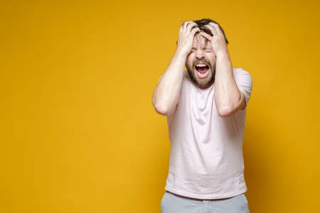 Caucasian man in stress, he clutches head and shouts loudly, closing eyes. Copy space.