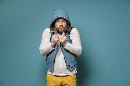 Attractive, bearded Caucasian man in a vest is very cold, he put a hood on head and looks at the camera in surprise. 스톡 콘텐츠