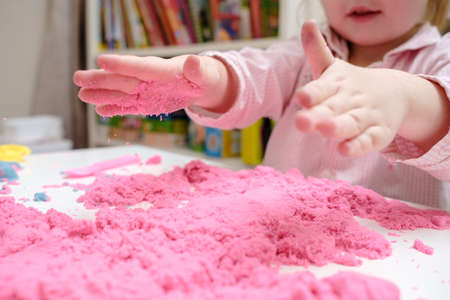 Enthusiastic child is playing with pink kinetic sand. Concept of developing fine motor skills and creative imagination in children.