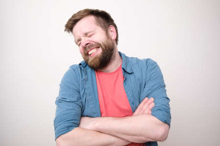 Funny shy man stands with crossed arms and smiles cute with eyes closed. White background.