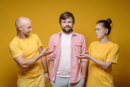Man and a woman look at their contented and smiling friend in bewilderment. Yellow background.