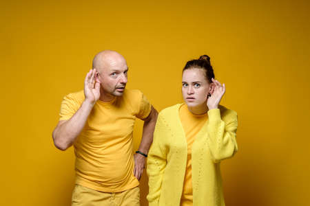 Alarmed man and woman in yellow t-shirts overhear someones conversations and stare fearfully into the camera. Studio.