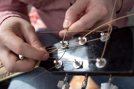 Hands male inserts new strings in an acoustic guitar. Repair of musical instruments.