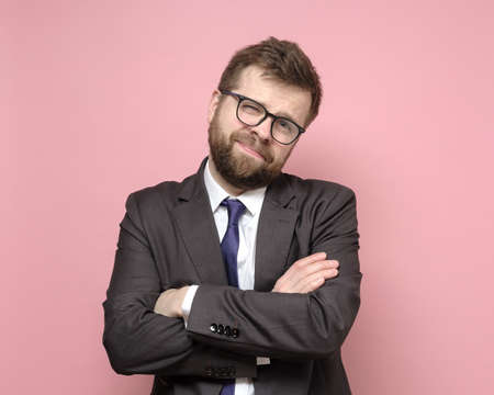 Friendly Caucasian bearded man in glasses and a suit stands with crossed arms and smiles cutely. Pink background.