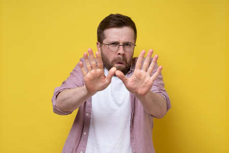 Frightened Caucasian man with glasses makes a stop gesture, he puts out palms and looks anxiously. Yellow background.