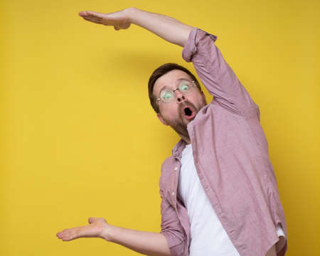 Surprised man in glasses shows a large size with hands, he exaggerates and looks at the camera in amazement. Copy space. Standard-Bild