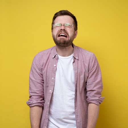 Sobbing, unhappy man in glasses and casual clothes, stands with hands down and eyes closed. Stress concept. Yellow background. Standard-Bild