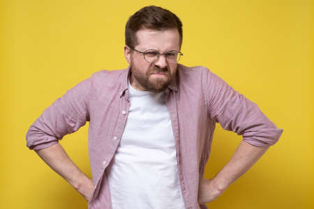 Disgruntled man in glasses and casual clothes stands akimbo and looks judgmental and vicious. Yellow background. Standard-Bild