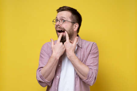 Caucasian man wearing glasses and casual clothes opened his mouth and shows missing tooth. Isolated, yellow background. Standard-Bild