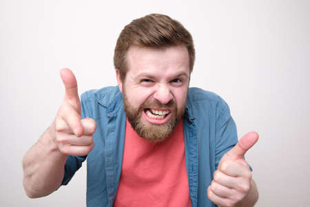 Strange bearded man makes a gesture with hands like it a gun and bares teeth. White background. Standard-Bild