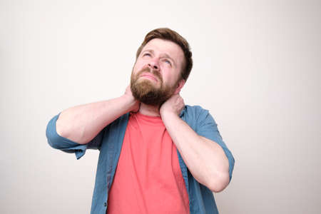 Caucasian man in casual clothes holds neck with hands and looks up with sadness. White background. Standard-Bild