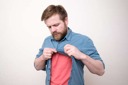 Focused bearded man unbuttons shirt after trying on. Shopping. White background.