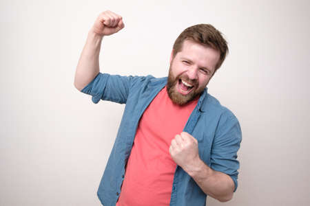 Cheerful, happy man, he laughs and makes a joyful hand gesture. Winning the lottery. Positive emotions. White background. Standard-Bild