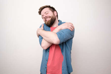 Charming bearded man hugs himself, he closed eyes and dreams of love, smiling sweetly. White background.