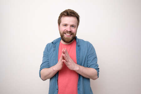 Smiling bearded man calmly and confidently looking at the camera with palms together. Isolated, white background.