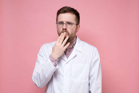 Alarmed young doctor in glasses and a white coat covered mouth with hand and looked fearfully into the camera. Pink background.