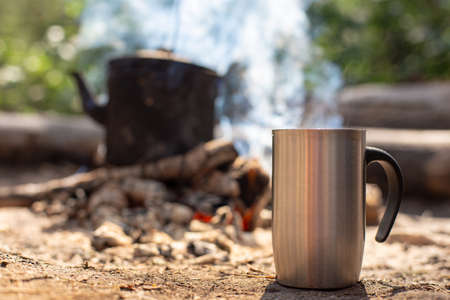 Metal mug with a hot drink stands on the ground, against the background of a campfire with a kettle, on a hike, in the forest.