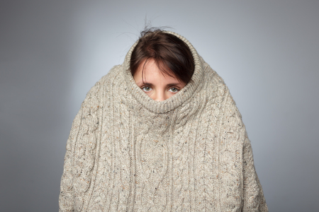 Girl pulls a large knitted sweater over her head. Despair and loneliness of depressed person Stockfoto