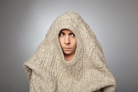 la chica sin maquillaje se esconde en el suéter enorme y parece infeliz a un lado, con los labios apretados