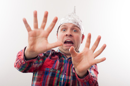 young man in a tin foil hat fearfully pulls palms forward. Afraid of radiation or aliens