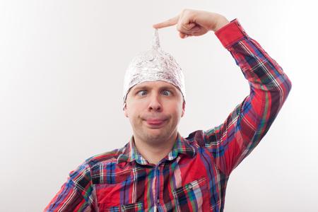 Jonge man in een tinfoliehoed vormt grappige gezichten. Bang voor straling of vreemdelingen Stockfoto - 74639681