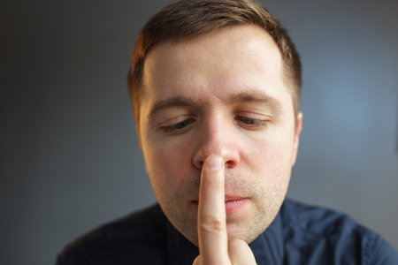 sobriety: The young man touches his finger to the tip of his nose. Check for sobriety after drinking alcohol Stock Photo