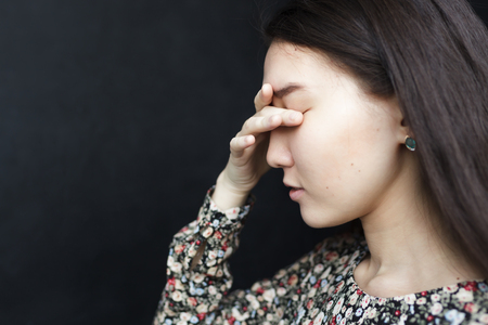 hand on forehead: Asian girl closes her eyes with her palm. Headache or migraine, suffer from depression and loneliness.