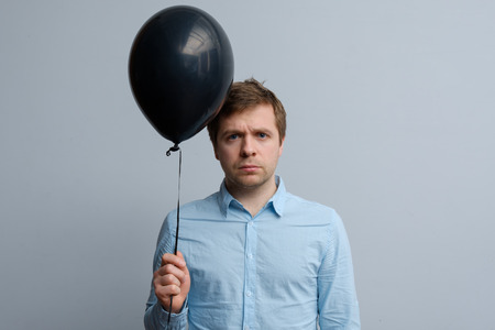 A sad young man in a blue shirt is holding a black balloon in his hands. Grieving and unwillingness to party